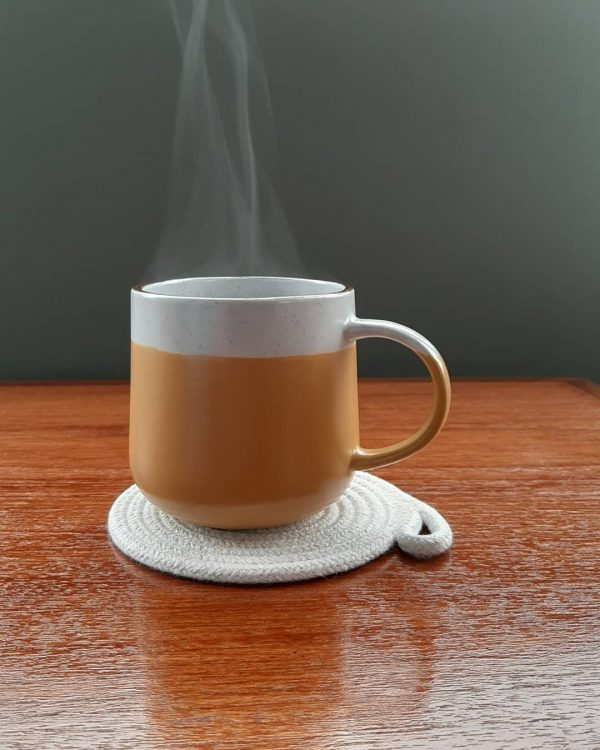 A mug of steaming coffee sits on an off white rope coaster