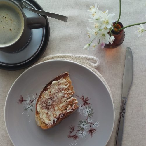 A table setting for breakfast. A cup of coffee, a plate with buttered toast, and a coiled rope placemat peaking out from under the plate
