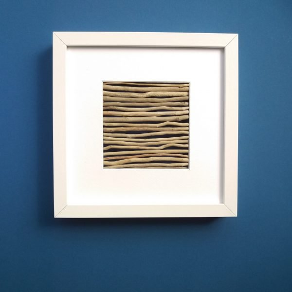 Against a bright blue background a white box frame with an arrangement of thin pale driftwood