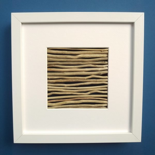 a white frame with thin pale driftwood in a close horizontal arrangement