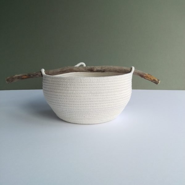a curved unbleached cotton rope bowl with a driftwood handle