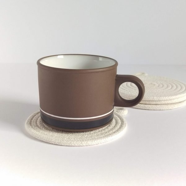 a squat brown vintage coffee cup sits on an off white rope coaster.